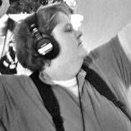 Kim checks the sound. A shotgun mic on a fishpole plugs into a mixer around her neck, then to a camera across the room.